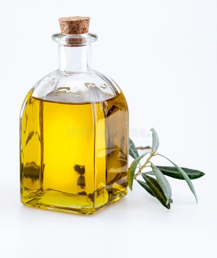 Aceite de oliva virginal adicional en la botella de cristal foreground Incluye las hojas y las ramas de olivo imagen de archivo libre de regalías