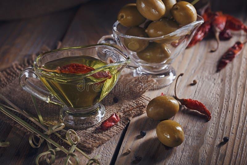 Aceite de oliva virginal adicional superior y aceitunas verdes con las hierbas frescas foto de archivo libre de regalías