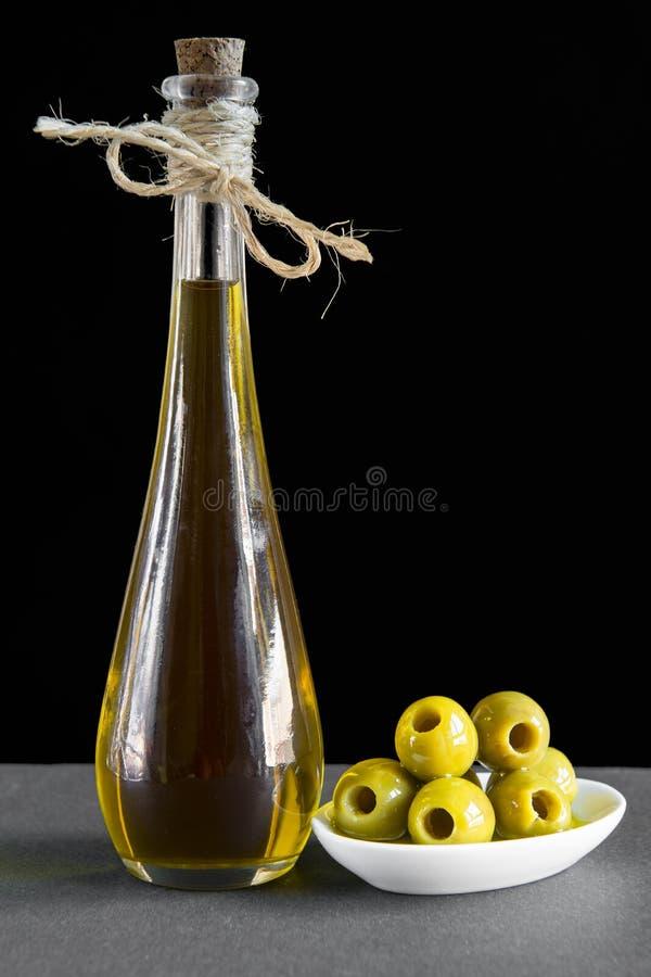 Aceite de oliva virginal adicional y aceitunas verdes marcadas con hoyos foto de archivo