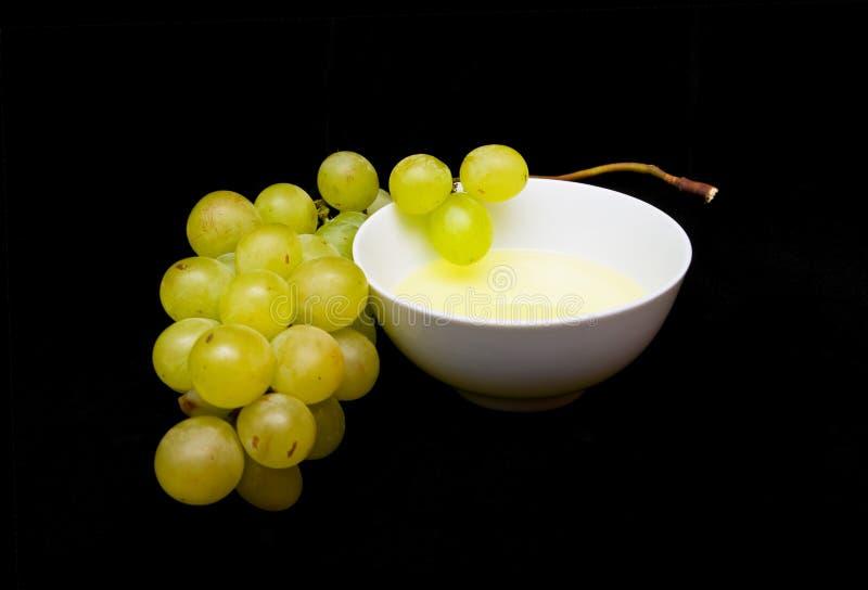 Aceite de semilla de la uva con un manojo de uvas blancas imagen de archivo