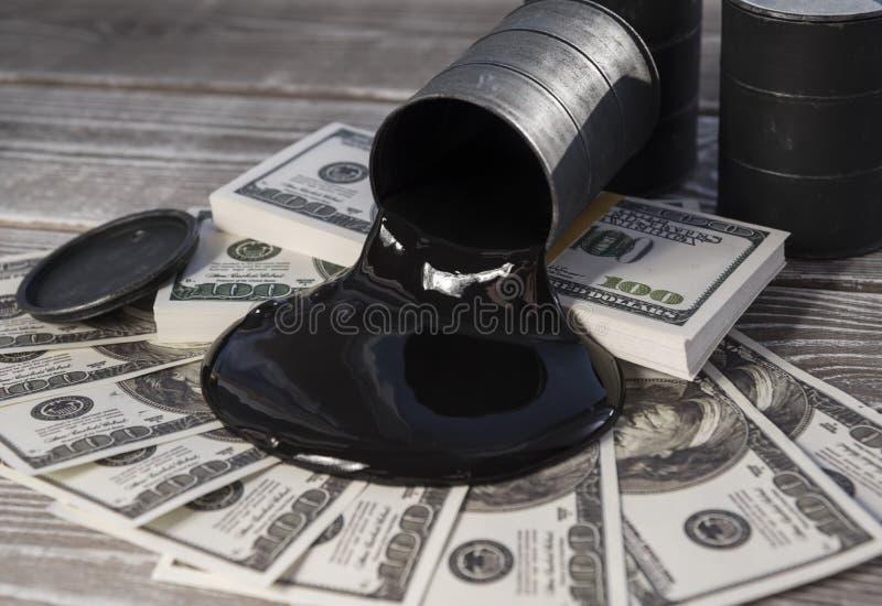 Aceite derramado de un barril a un billete de dólar del dinero foto de archivo libre de regalías