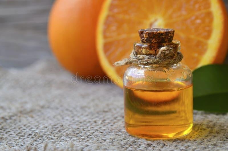 Aceite esencial anaranjado en una botella de cristal para el cuidado de piel, el balneario, la salud, el masaje, el aromatherapy  foto de archivo libre de regalías