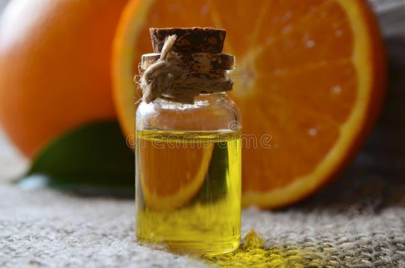 Aceite esencial anaranjado en una botella de cristal para el cuidado de piel, el balneario, la salud, el masaje, el aromatherapy  imágenes de archivo libres de regalías