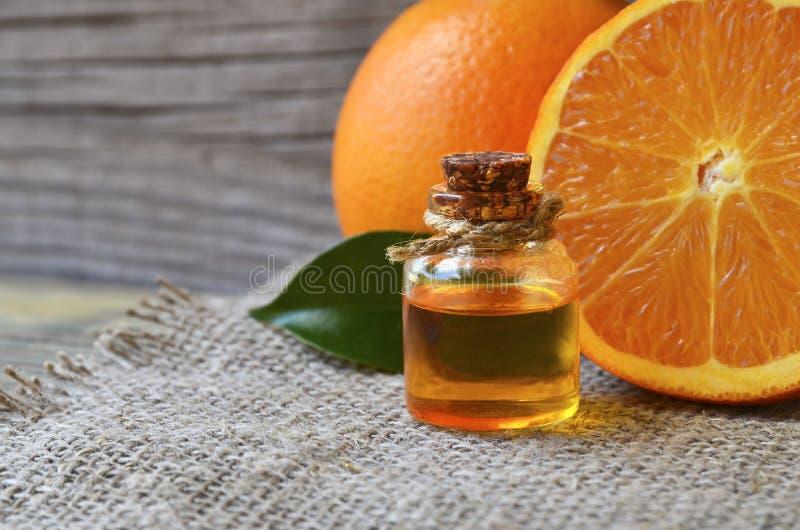 Aceite esencial anaranjado en una botella de cristal para el cuidado de piel, el balneario, la salud, el masaje, el aromatherapy  foto de archivo