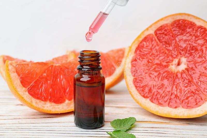 Aceite esencial de la fruta cítrica del goteo en la botella fotos de archivo