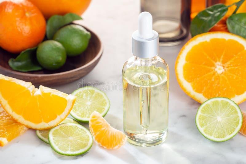 Aceite esencial de la fruta cítrica Aceite de la fruta cítrica en la botella de cristal Productos para el cuidado de la piel fotos de archivo libres de regalías