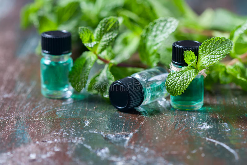 Aceite esencial de la hierbabuena en pequeñas botellas, menta verde fresca en fondo de madera imagenes de archivo