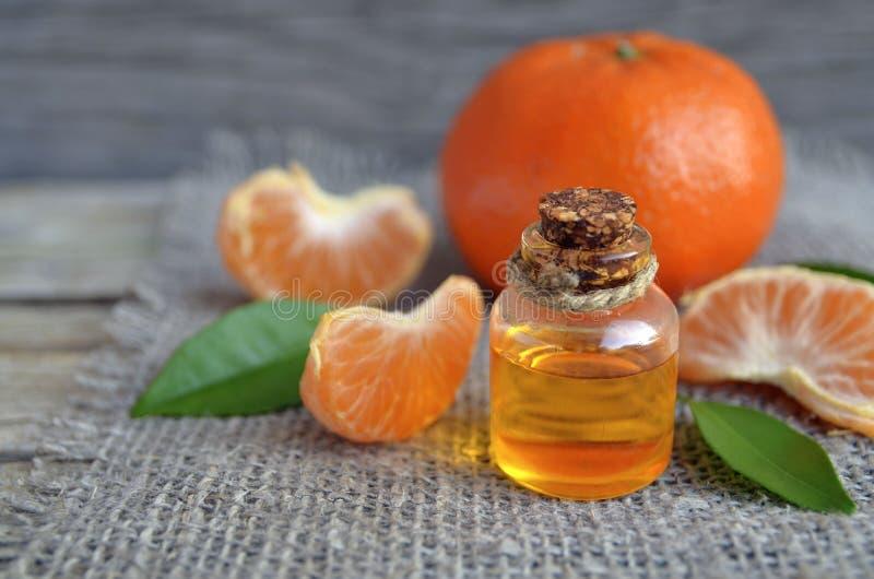 Aceite esencial de la mandarina en una botella de cristal con la fruta fresca del mandar?n en la tabla de madera vieja foto de archivo