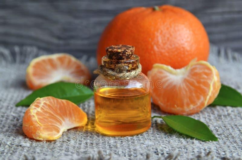 Aceite esencial de la mandarina en una botella de cristal con las frutas frescas en la tabla de madera vieja fotos de archivo