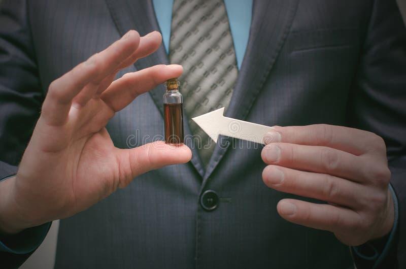 Aceite esencial de la píldora azul en las manos masculinas Opción correcta de medicamentos foto de archivo