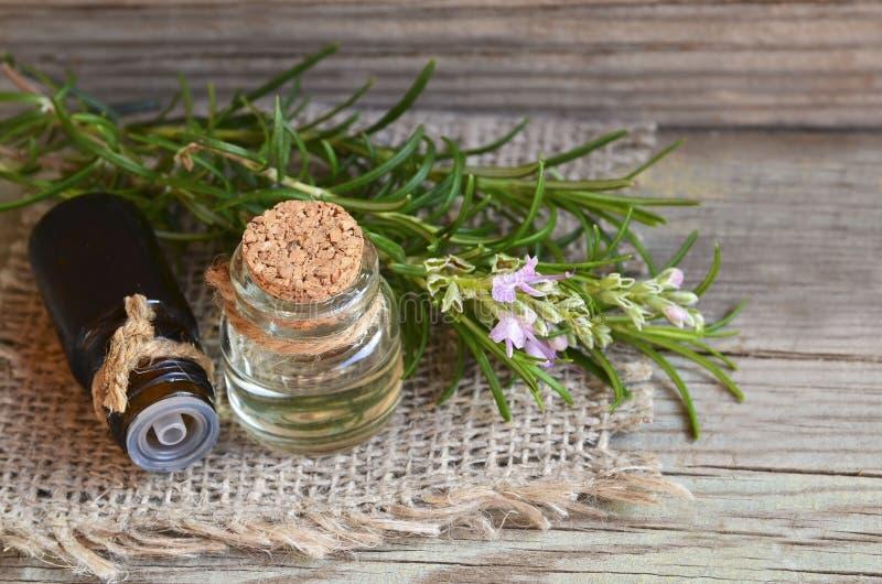 Aceite esencial de Rosemary en una botella de cristal del dropper con la hierba verde fresca del romero en la tabla de madera vie foto de archivo libre de regalías