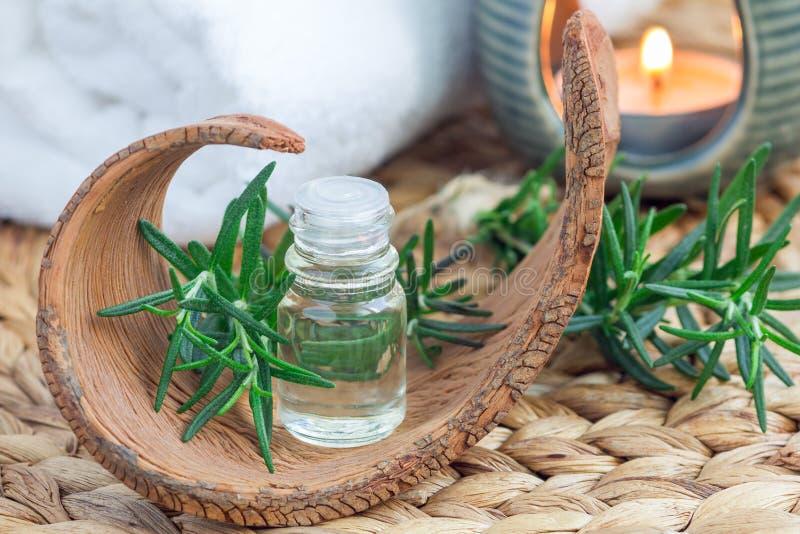 Aceite esencial de Rosemary en vidrio en la estera tejida con el fondo del balneario imagenes de archivo