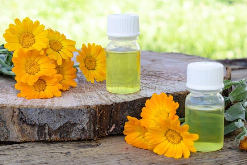 Aceite esencial del Calendula cerca de las flores amarillas del calendula en un fondo de madera en naturaleza Extracto de tinte d fotos de archivo