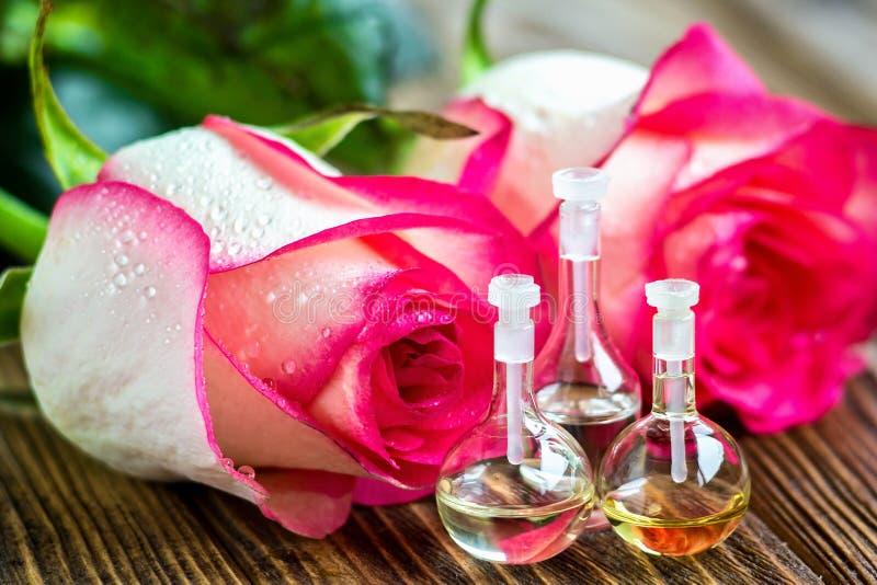 Aceite esencial en la botella de cristal con las flores color de rosa en fondo de madera Pequeñas botellas de perfume Tratamiento imagenes de archivo