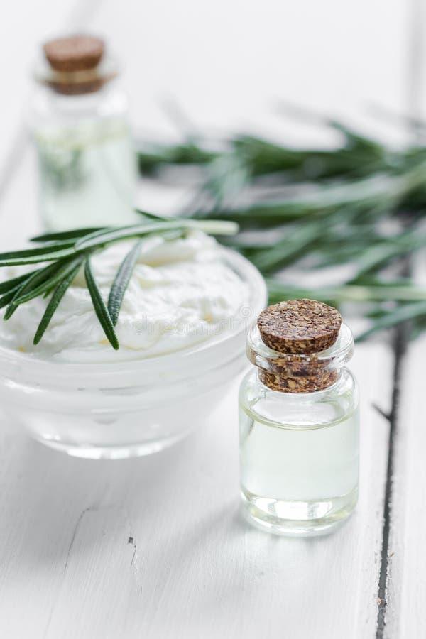 Aceite esencial natural del aroma con romero en fondo de madera de la tabla imágenes de archivo libres de regalías