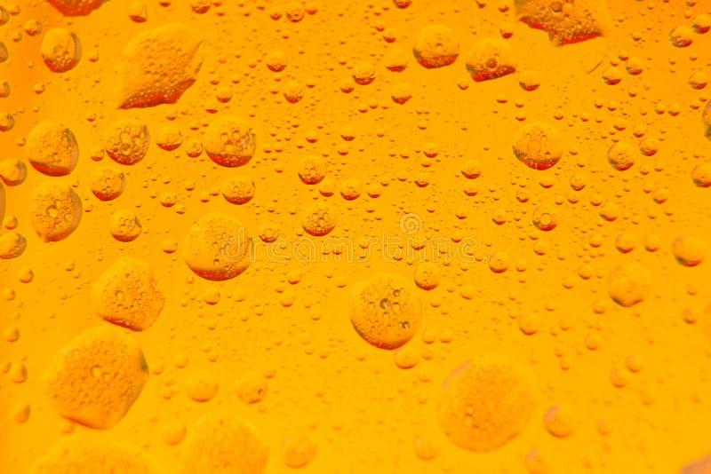 Aceite mezclado en agua en un fondo amarillo-naranja y de oro colorido Fotografiado en cierre para arriba con el DOF bajo Foto to foto de archivo libre de regalías