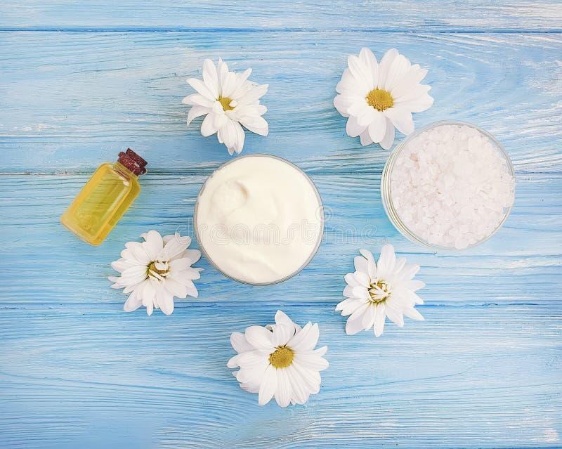 Aceite poner crema cosmético de la frescura, crisantemo de la sal en fondo de madera imágenes de archivo libres de regalías