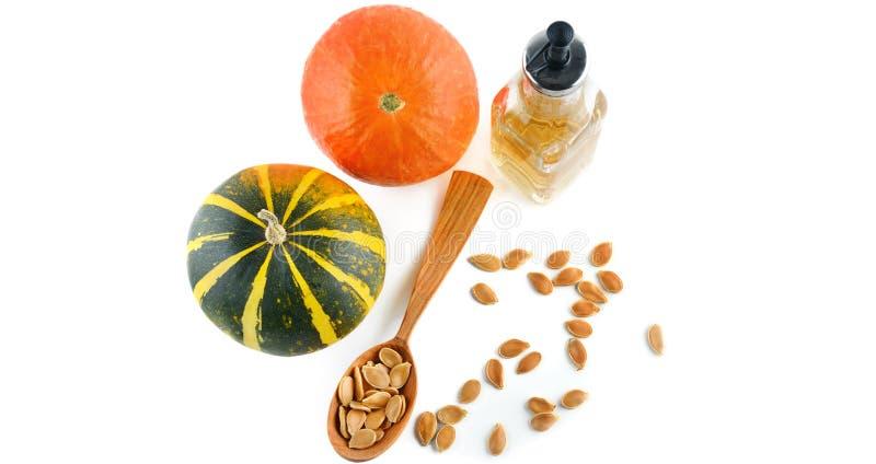 Aceite, semillas y frutas de la calabaza aisladas en el fondo blanco wide imagen de archivo libre de regalías