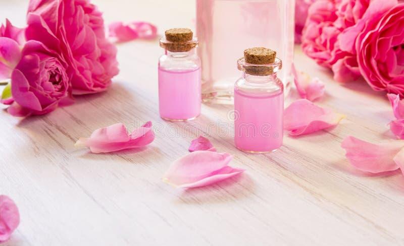 Aceite y agua de Rose con las flores rosadas brillantes en el fondo de madera blanco, foto de archivo