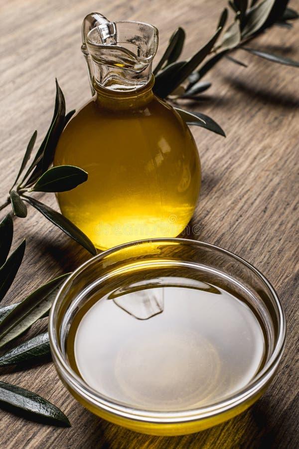 Aceite y hojas de oliva en una tabla de madera fotografía de archivo