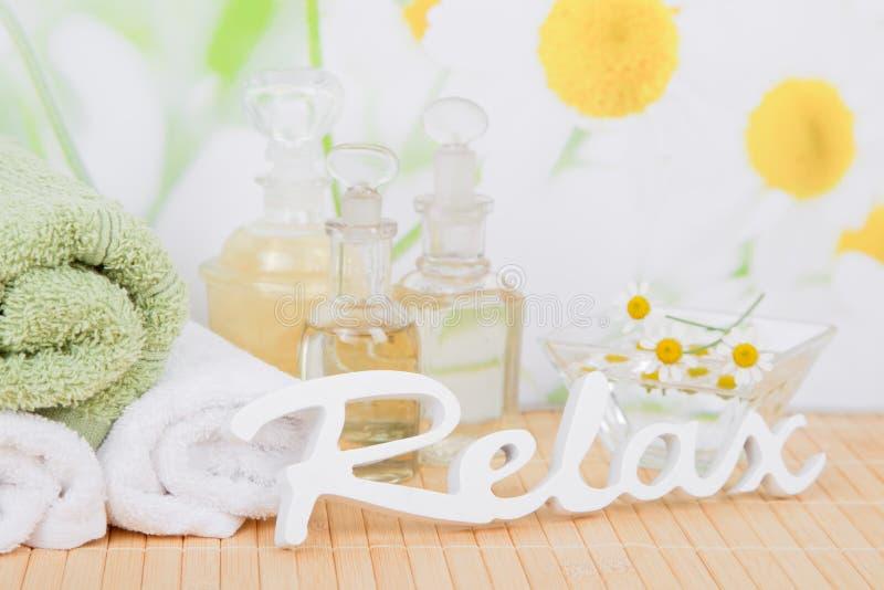 Aceite y manzanilla con las toallas para el tratamiento del ayurveda fotografía de archivo