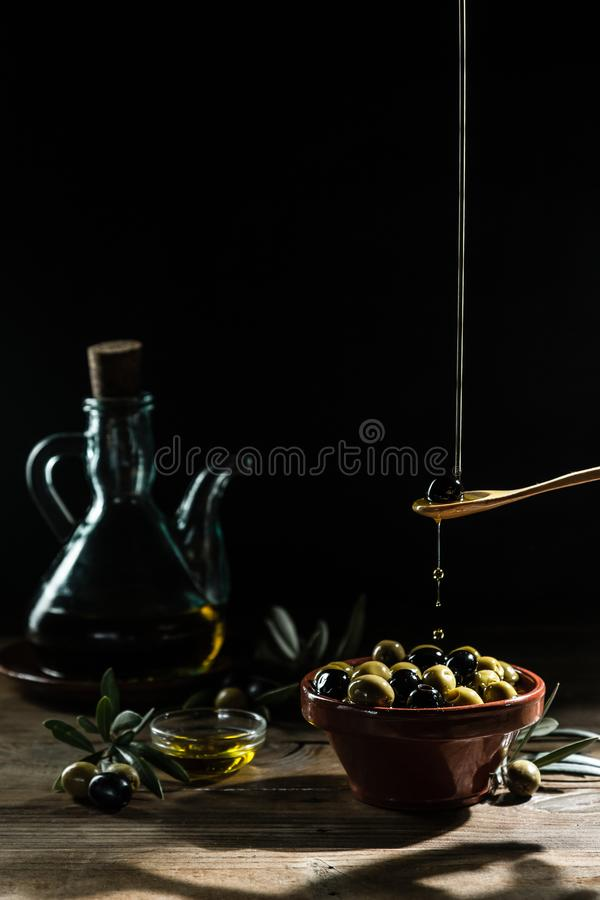 Aceite y rama de olivo de oliva en el vector de madera fotos de archivo libres de regalías