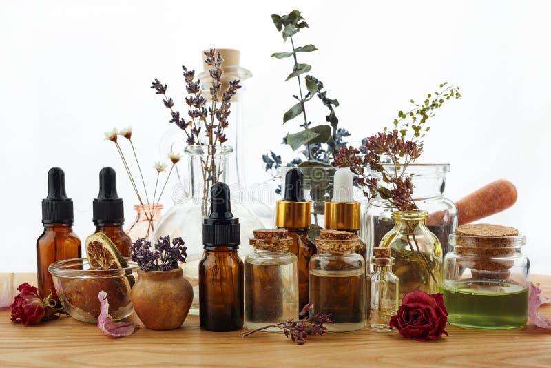 Aceites esenciales con las hierbas y las flores en la tabla de madera imagen de archivo libre de regalías