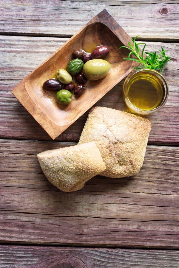 Aceitunas conservadas en vinagre con pan y aceite de oliva en una tabla rústica foto de archivo libre de regalías
