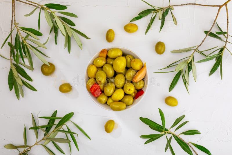 Aceitunas del artesano conservadas en aceite de oliva virginal adicional, vinagre, especias con las pimientas rojas y ajo imagenes de archivo
