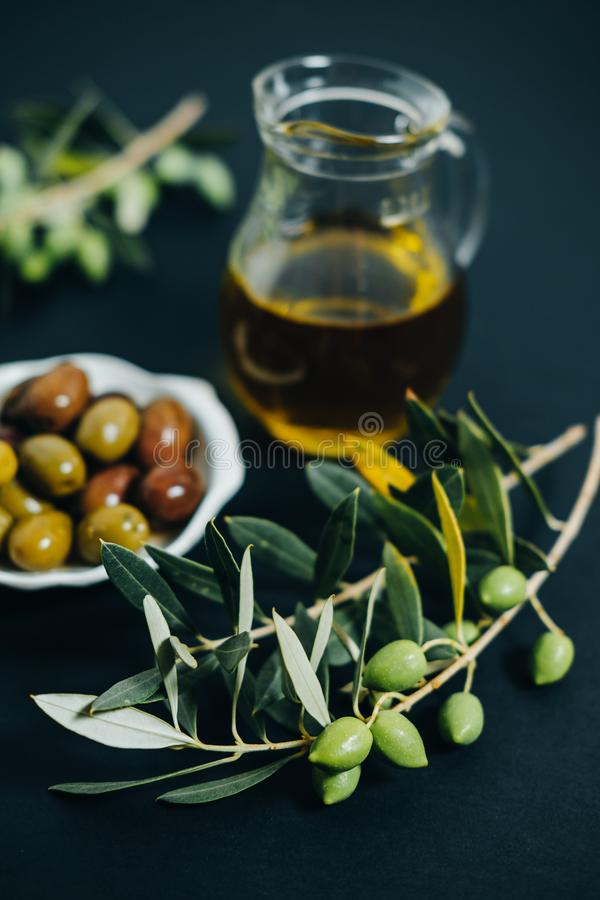 Aceitunas frescas, aceite y rama verde en fondo negro fotos de archivo