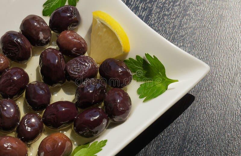 Aceitunas negras en una placa blanca con aceite de oliva imagen de archivo libre de regalías