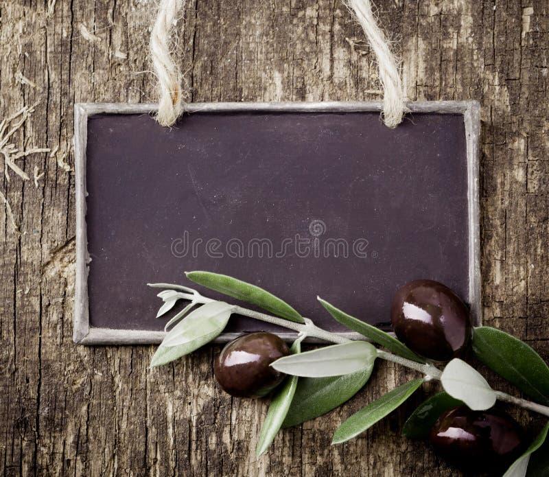 Aceitunas negras frescas y una pizarra en blanco foto de archivo libre de regalías