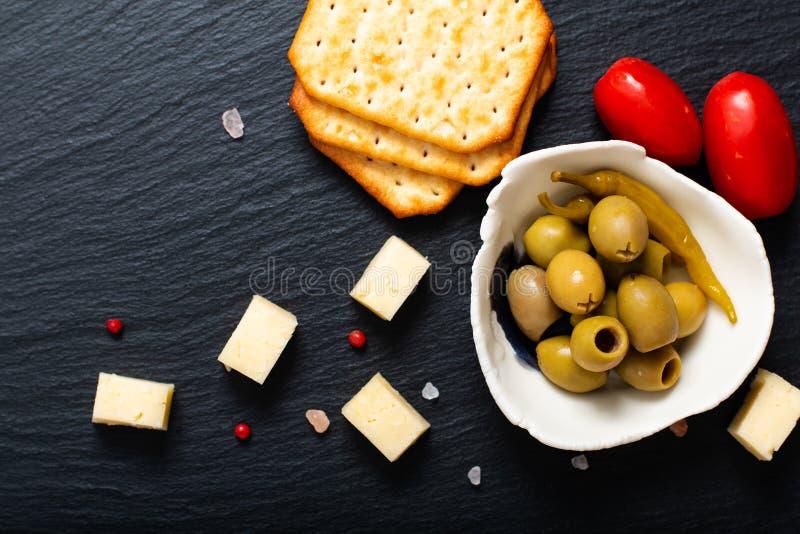 Aceitunas queso, tomates y galleta del aperitivo de la comida en el listón negro foto de archivo libre de regalías