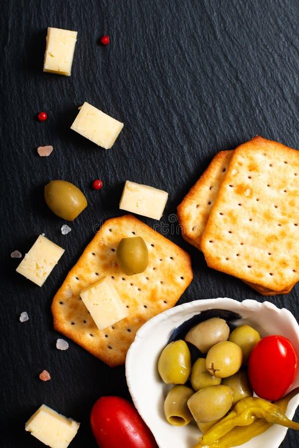 Aceitunas queso, tomates y galleta del aperitivo de la comida en el listón negro fotografía de archivo