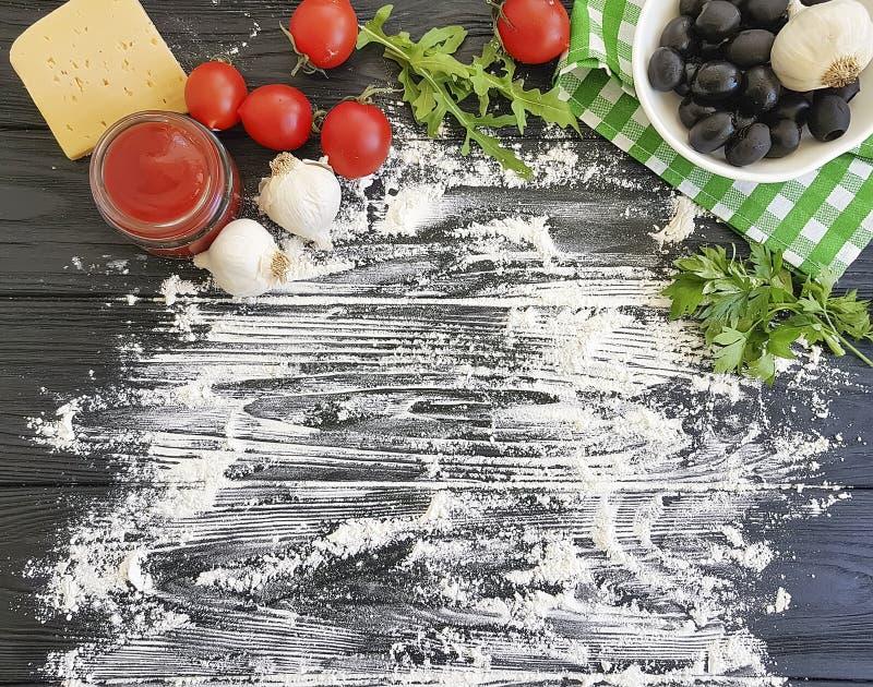 Aceitunas, tomates, ajo, verdura fresca de la cena del ingrediente de la harina de la salsa de tomate que se prepara en un marco  foto de archivo