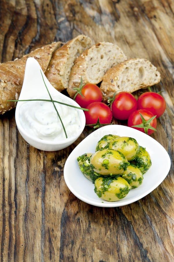 Aceitunas verdes con pan fresco e hierbas imagenes de archivo