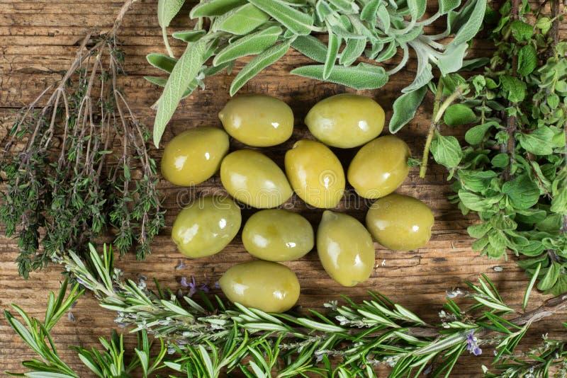 Aceitunas verdes con varias hierbas alrededor en la tabla de madera fotografía de archivo libre de regalías
