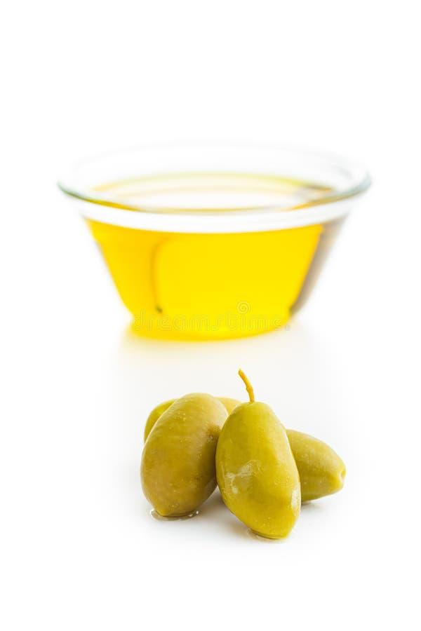 Aceitunas verdes y aceite de oliva en bol de vidrio fotos de archivo