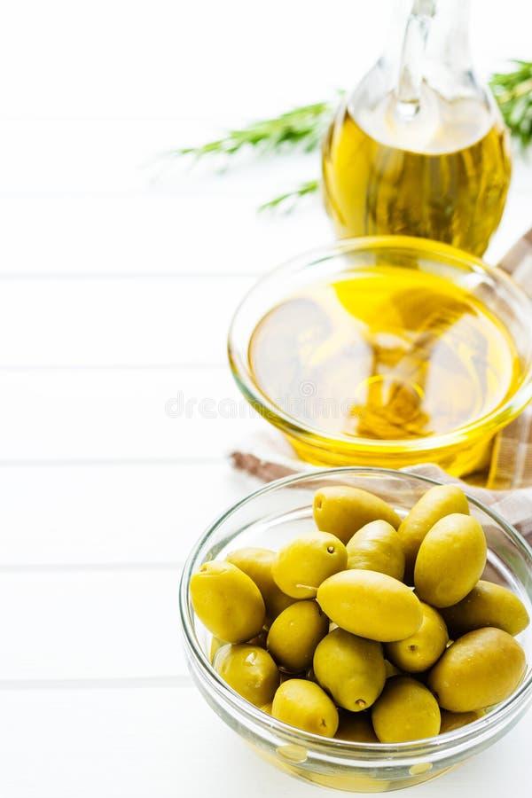 Aceitunas verdes y aceite de oliva en bol de vidrio foto de archivo libre de regalías
