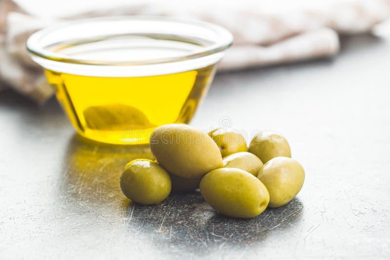 Aceitunas verdes y aceite de oliva en bol de vidrio imágenes de archivo libres de regalías