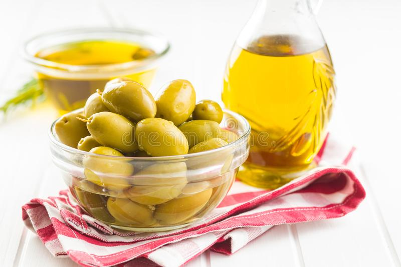 Aceitunas verdes y aceite de oliva en bol de vidrio imagen de archivo
