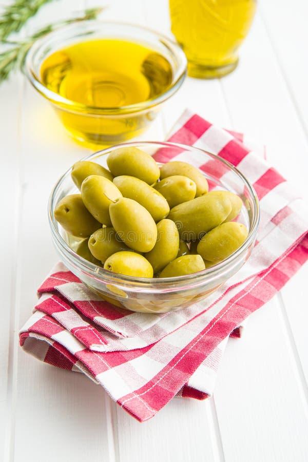 Aceitunas verdes y aceite de oliva en bol de vidrio foto de archivo