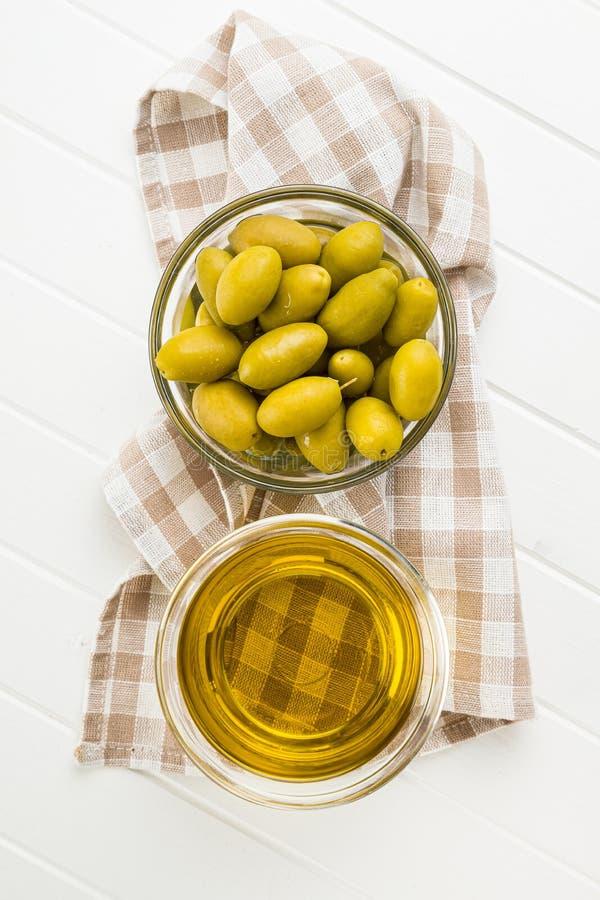 Aceitunas verdes y aceite de oliva en bol de vidrio imagenes de archivo