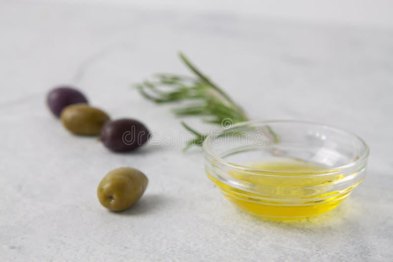 Aceitunas y aceite de oliva con las hierbas en un fondo neutral imagen de archivo