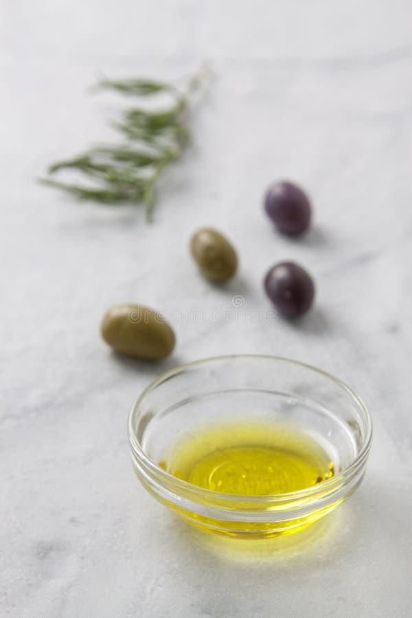 Aceitunas y aceite de oliva con las hierbas en un fondo neutral con la profundidad del foco limitada fotografía de archivo