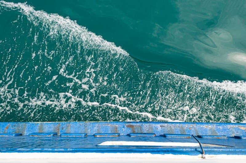 Acena e espirra no lado que flutua rapidamente no barco oxidado velho do mar fotografia de stock royalty free