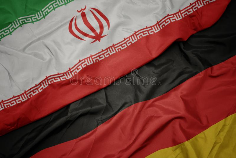 acenando bandeira colorida da Alemanha e bandeira nacional do Irã fotografia de stock royalty free