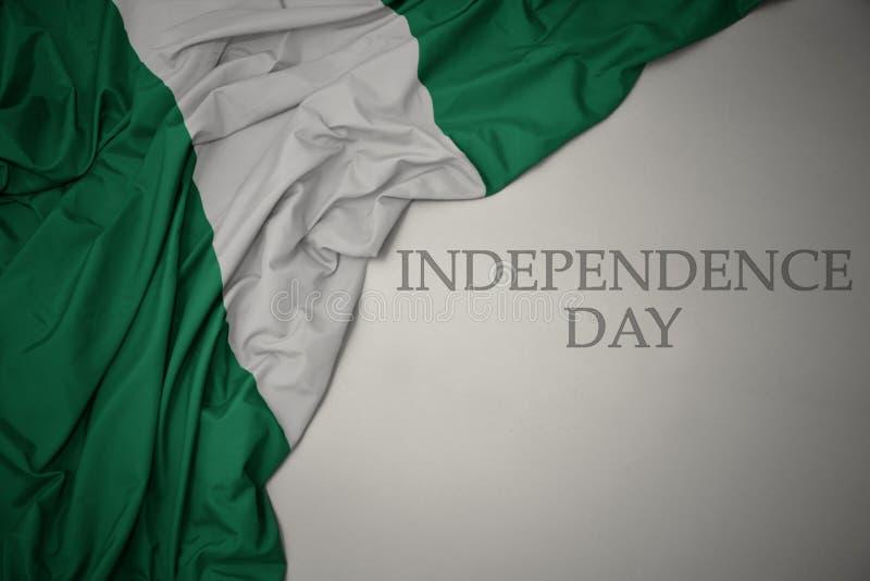 acenando a bandeira nacional colorida da nigéria em um fundo cinza com o dia da independência do texto imagens de stock