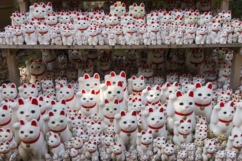 Acenando o gato, Maneki Neko em Gotokuji no Tóquio do templo imagem de stock