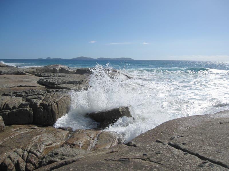 Acene batendo a costa e a praia rochosas australianas com rochas gigantes fotos de stock royalty free